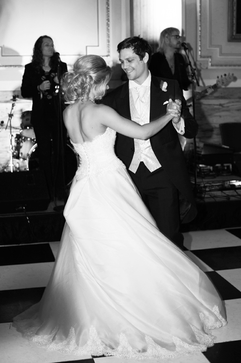 Black and white shot of happy couple dancing in front of band