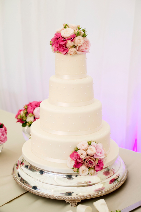 Four tiered white iced wedding cake with flower decorations