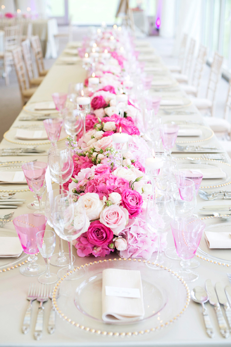 Floral table runner of roses and glassware in shades of pink