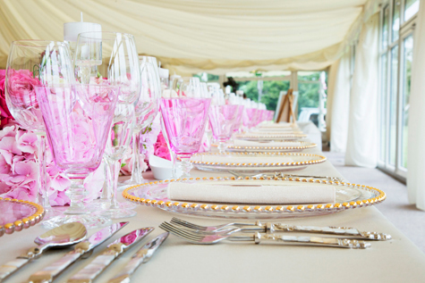 Close-up shot of crockery, cutlery and glasses on table in marquee