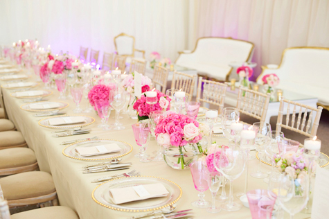 Shot of long table in marquee decorated with pink flowers, crockery, silver cutlery and glassware