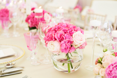 detail shot of pink and white roses in round vases on table