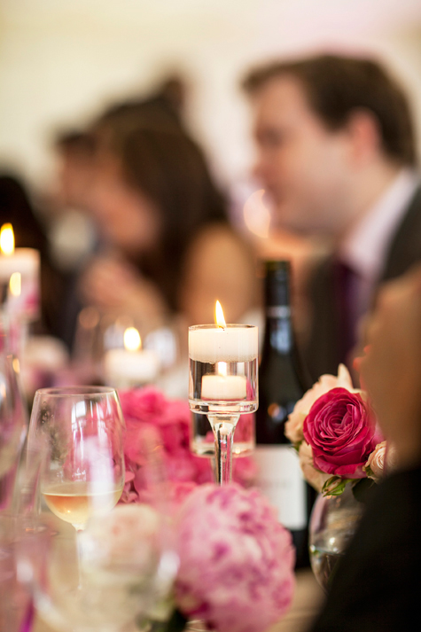 Detail shot of guests at table with candles and flowers in foreground