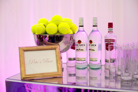 Shot of 'Pete's Bar' sign with tennis balls in silver bowl, bottles of spirits and glasses