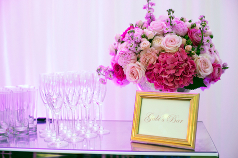 Shot of 'Gabi's Bar' sign with pink flower arrangement and champagne flutes