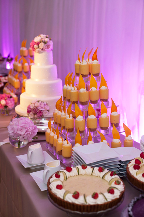 Shot of cake table with flowers, wedding cake in centre and pyramid of smaller desserts alongside