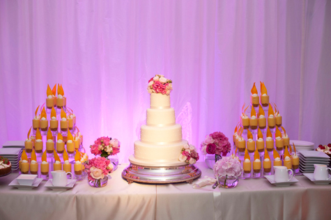 Front facing shot of wedding cake table with wedding cake flanked by pyramids of smaller cakes and flowers