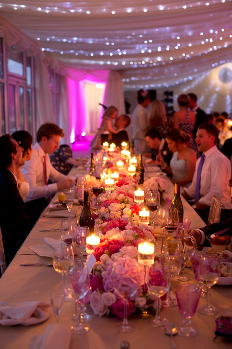 long table shot of guests eating and talking with candles lighting up marquee