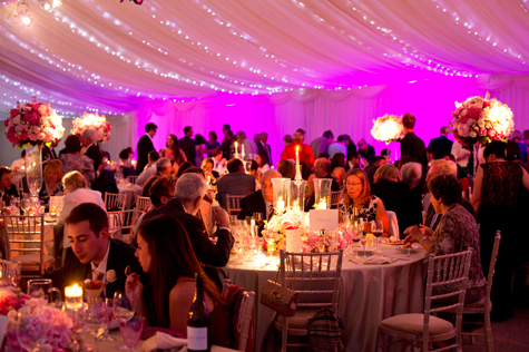 Interior of marquee lit with pink lights, fairy lights on ceiling and candles with guests at tables