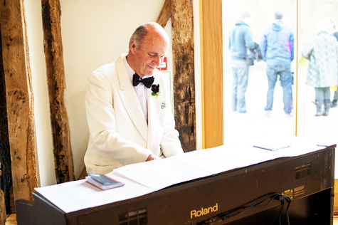 Gentleman in white tuxedo playing electric keyboard