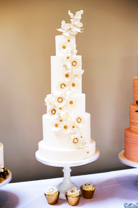 Front shot of tall, white, tiered wedding cake with pale white flower decorations on front and cupcakes in foreground