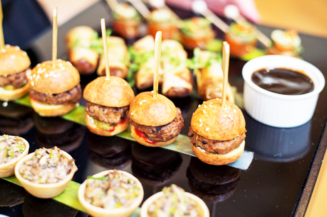 close-up shot of canapés including mini-burgers, duck spring rolls with dipping sauce and mushroom tartlets