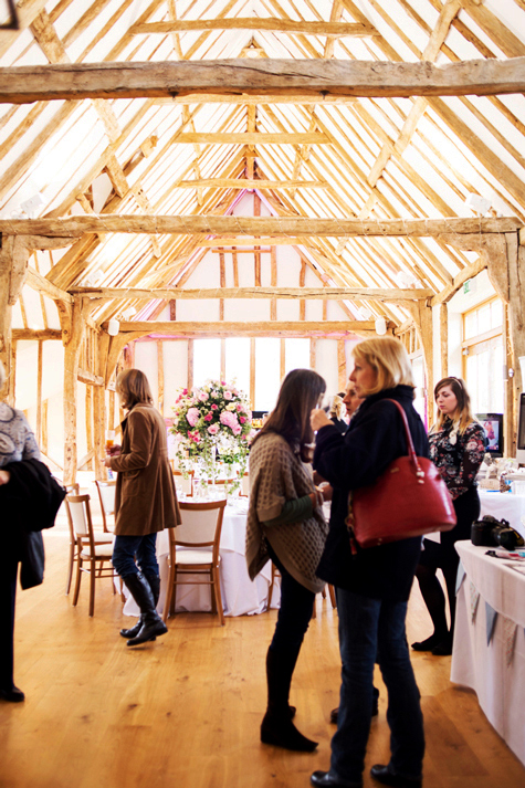 Interior shot of reception barn with timber ceilings and guests milling about