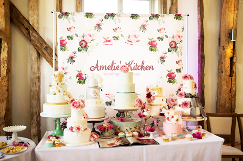 Shot of Amelie's Kitchen Wedding cake supplier with different cakes on cake stands and floral signage behind