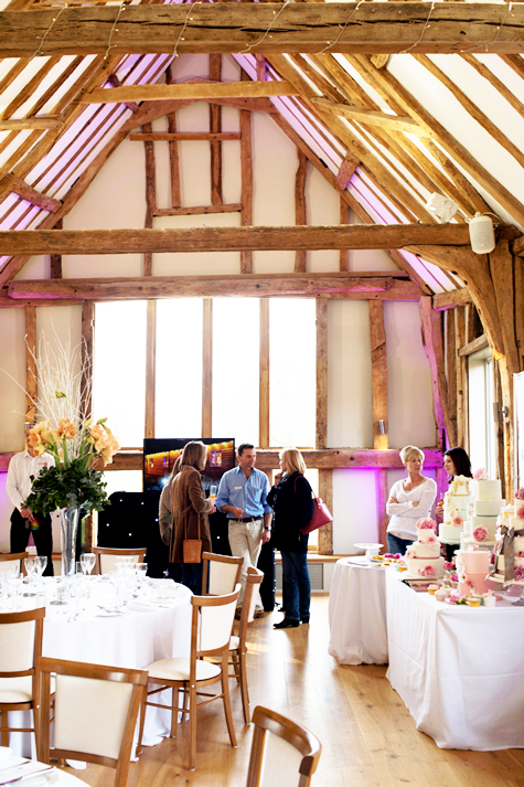 Interior shot of people in reception barn with dressed tables, timber beams and sunlight through window