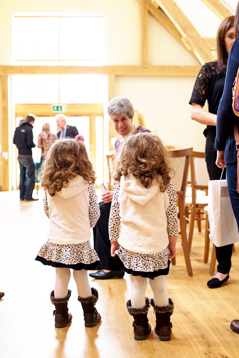 Identical twin little girls talking to supplier, photographed from behind
