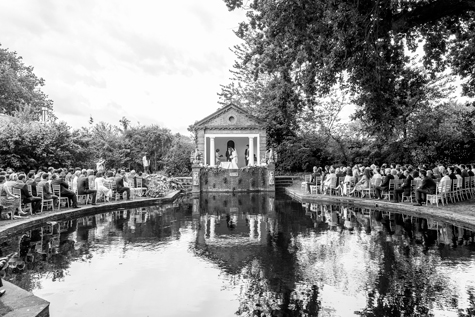 Black and white image of pond, ceremony and seated guests