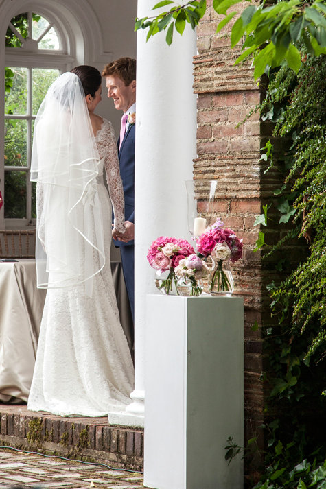 Bride and Groom in pagoda during ceremony with vase of flowers in foreground