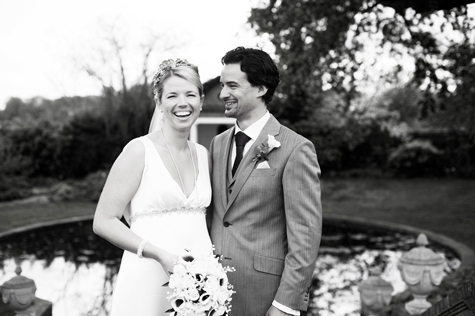Black and white image of bride and groom outside by pond