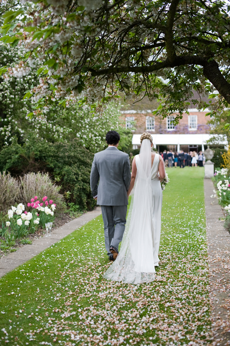Bride and Groom walking through gardens photographed from behind