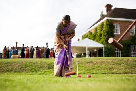 Indian lady playing boules outside marquee