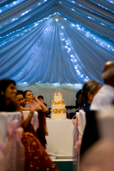 Interior of marquee with blue ceiling drapes, wedding cake in centre and guests sitting at tables