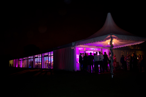Exterior of marquee at night with pink lighting and guests outside