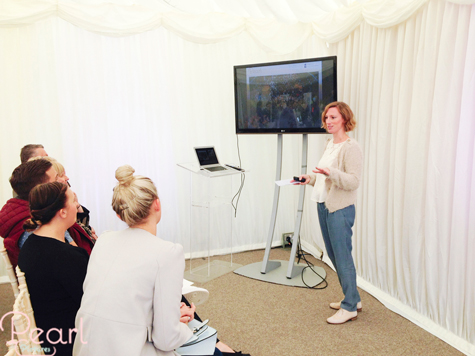Jemma giving talk on wedding photography in front of guests in marquee
