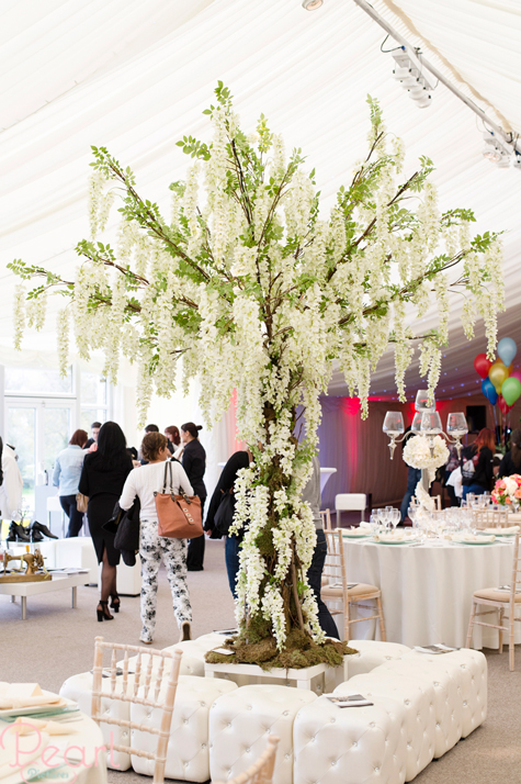 Interior of marquee with decorated tree in centre and guests browsing