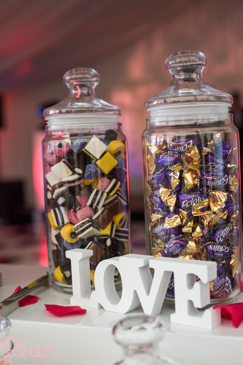 Detail shots of two sweet jars filled with liquorice all sorts and chocolate eclairs and the letters LOVE propped up below