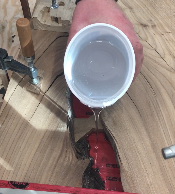 Pouring epoxy to fill a void.