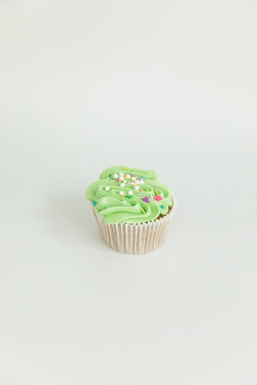 vanilla cupcake with colorful frosting and sprinkles
