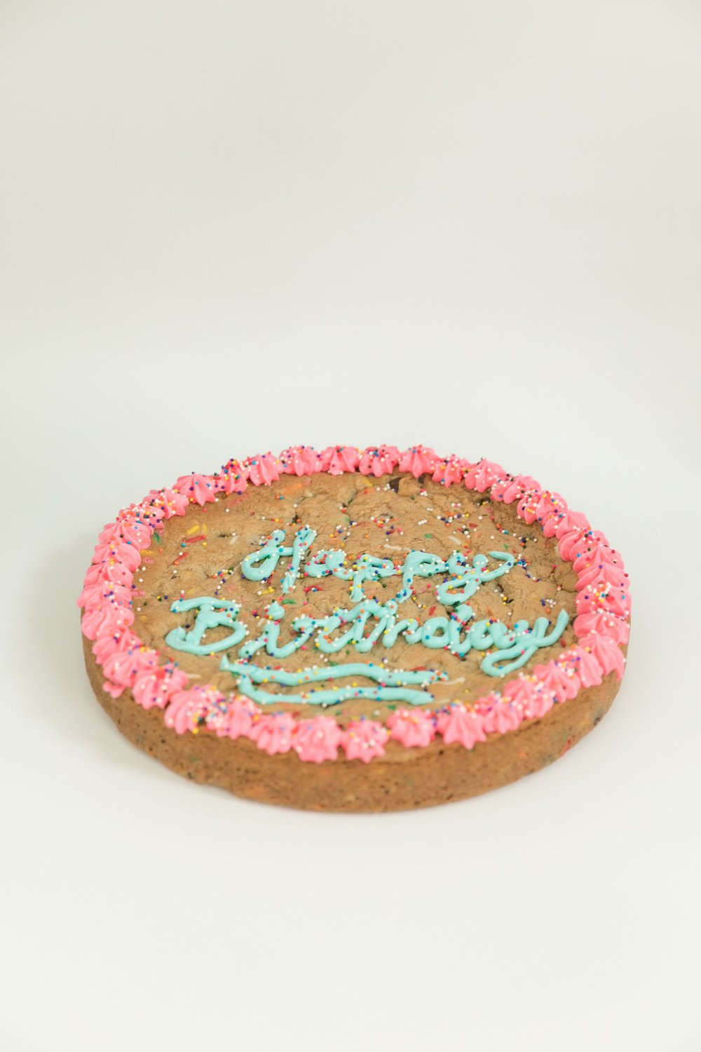 Happy Birthday chocolate chip cookie cake with lots of sprinkles and vanilla buttercream frosting