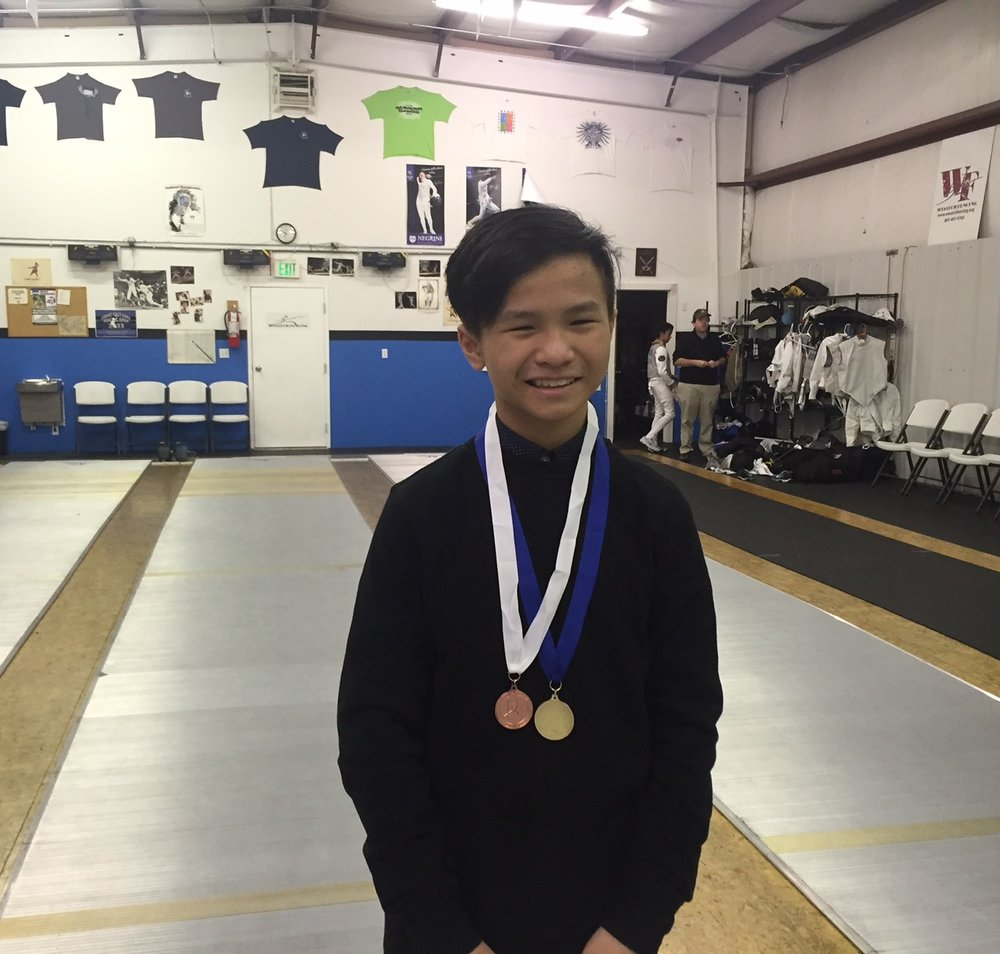 Medals for a youth fencer at an RYC