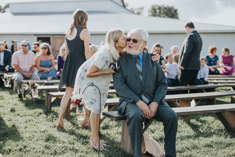 we look out for candids - We are always on our toes. Photo's like these are the moments you wouldn't see. As the guests arrived at Bailey and Tyler's wedding, the brides mother planted a quick kiss on Bailey's grandfather's cheek.