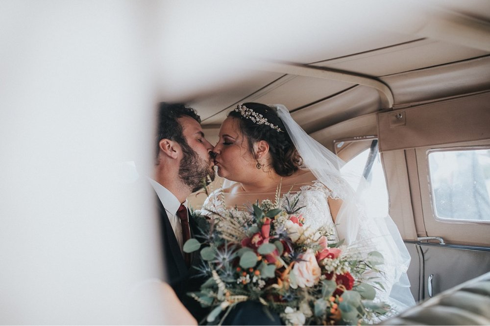 Newlyweds sharing a kiss in their getaway car.