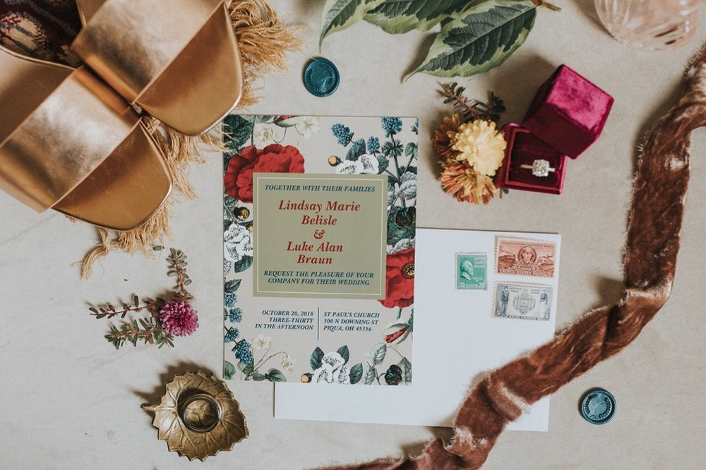 A photo of a wedding invitation, rings, and wedding shoes.