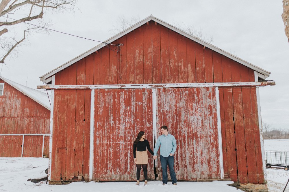 Couple standing in front of a barn