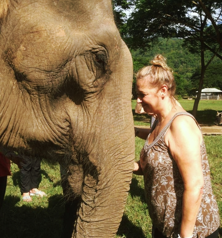 Tara Cindy Sherman rests her forehead on an elephants trunk.