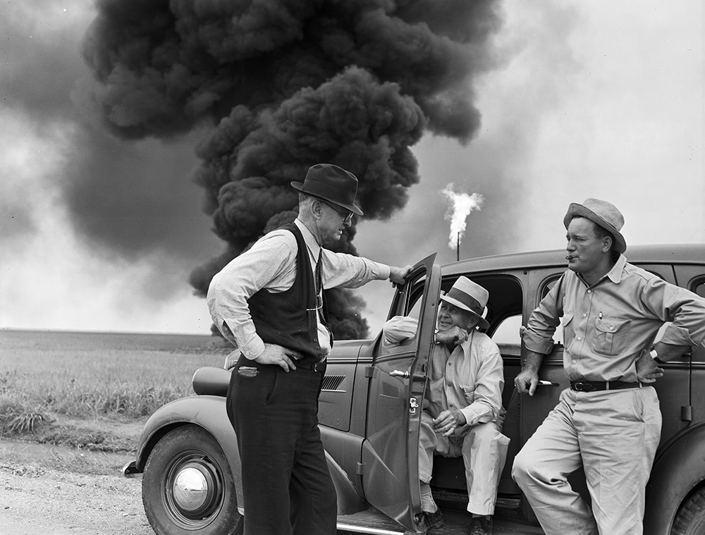 John_Butler_talks_with_two_men_while_oil_well_fire_burns_in_background_(9238328229).jpg
