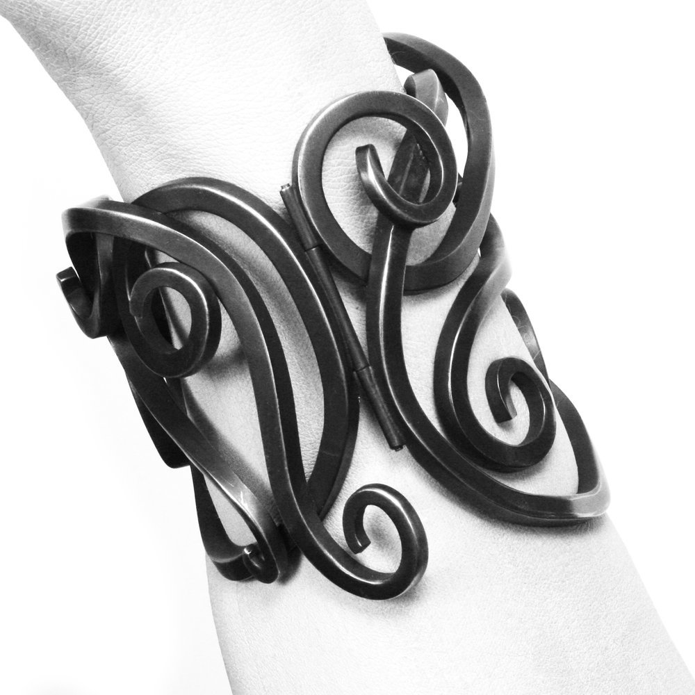 Armored up, beautifully. It's heavy, you definitely won't forget you are wearing it, and nobody who meets you will fail to notice. The love child of an Art Nouveau master and the local blacksmith, in silver, which has been subversively blackened.