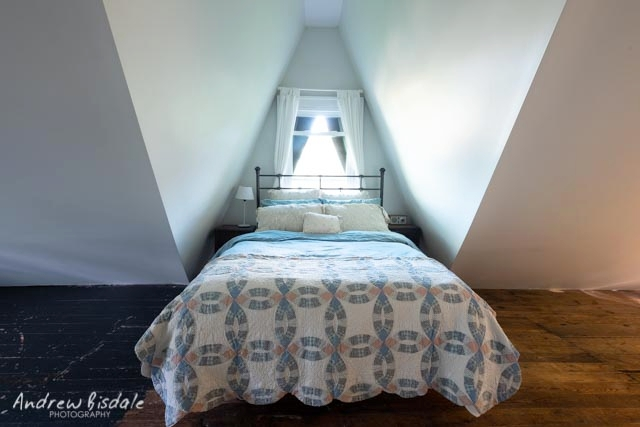 The Loft - The Loft is our private suite on the 3rd Floor. A queen-sized bed sits nestled in the center gable of the house. Original flooring and stained glass add Gothic accents to this space.