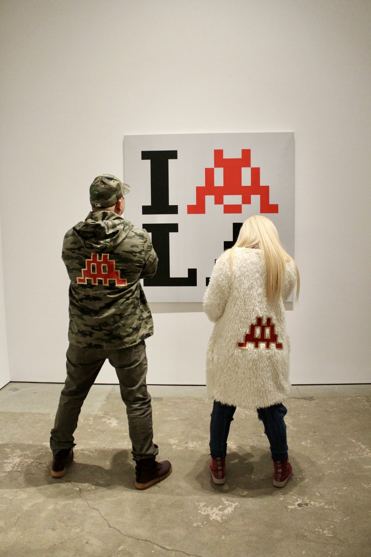 Stylish LA couple admiring Invader art by Roger Martinez