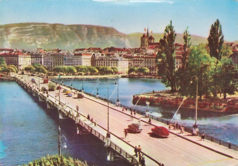 Vintage postcard of Geneva with a view of the Mont Blanc bridge with a few cars and the Salève in the background.