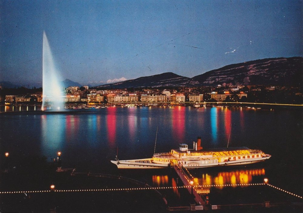 Vintage postcard of Geneva with a view of Lac Léman and a paddle boat, the Jet d'Eau, la Rade with colourful lights and the Salève.