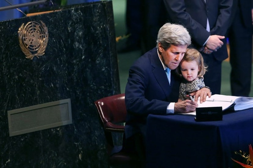 U.S. Secretary of State John Kerry signs the Paris Agreement while his granddaughter looks on.