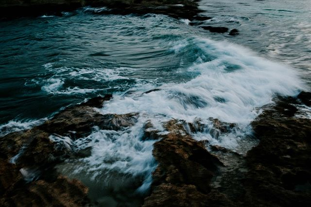 This photo was taken in Tulum, Mexico.  @mattthew.mayer and I climbed onto these rocks along the coast to watch the sunset while some locals were fishing. The two of us were sharing a bottle of champagne and building a makeshift tripod with some rocks and whatever else we could find. We weren't very successful so this long exposure photo is blurry but I really like it. I wanted to capture some movement with the water crashing on the rocks. I just got it printed on bamboo to hang in my home and to remember our silly night hanging on some rocks in Tulum.