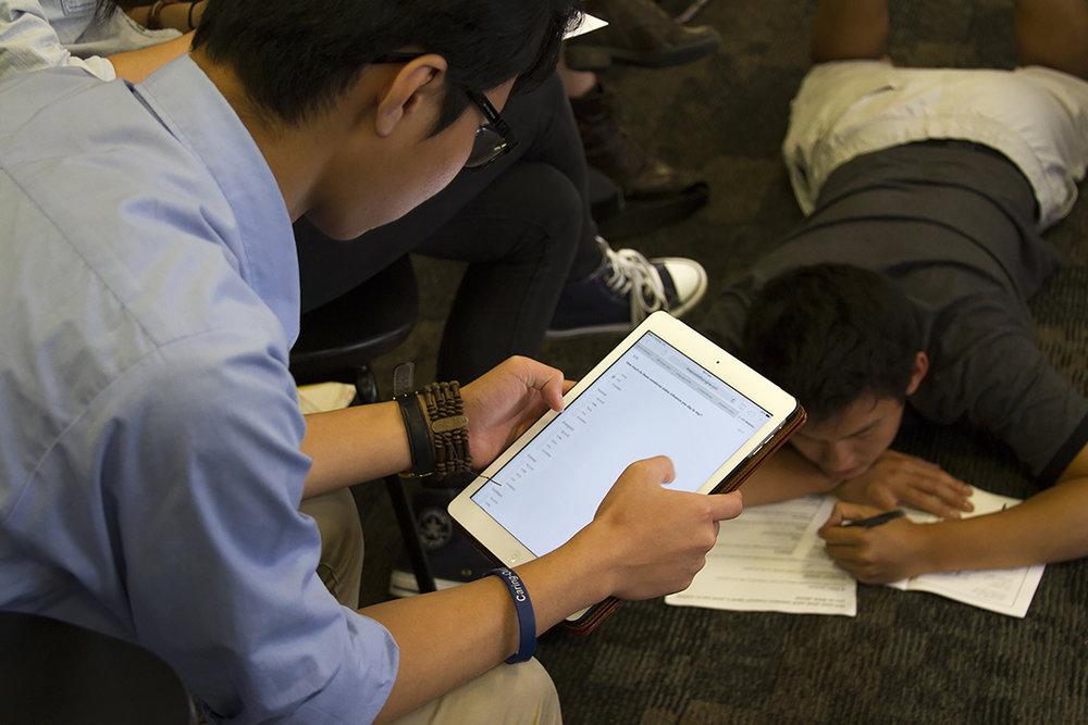Conference participants filling out paper and digital surveys.