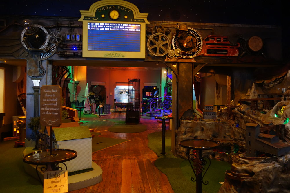 Urban Putt San Francisco - Indoor Miniature Golf Course, Game Room and Restaurant  Sound Design, Mix & Installation  A machine room solid-state player runs 18 channels of non-interactive audio to the various rooms, while more than 15 stereo  digital audio repeaters with built-in amplifiers are spread locally throughout the course for interactive sounds.  Subwoofers and transducers are used for special effects such as earthquakes and floor movement while an audio-animatronic skeleton gives out instructions for a Día de Muertos hole.