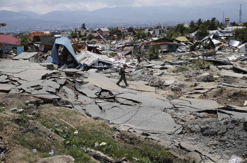 2.People survey the damage following a massive earthquake and tsunami at Talise beach in Palu, Central Sulawesi, Indonesia, Monday, Oct. 1, 2018. Bright-colored body bags were placed side-by-side in a freshly dug mass grave Monday, as a hard-hit Indonesian city began burying its dead from the devastating earthquake and tsunami. (AP Photo/Tatan Syuflana)